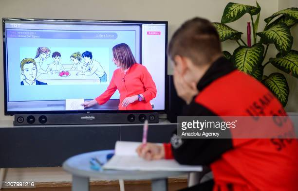 A primary school student watches his lecture from the TV at his house within the distance education program on March 23 2020 in Usak Turkey Turkey...
