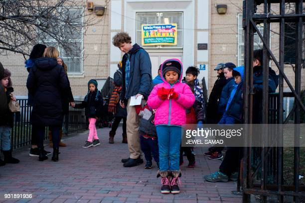 Primary school students accompanied by their parents and guardians gather outside their school in New York on March 14 to take part in a national...