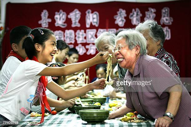 Primary school students feed the elderly guests with noodles to celebrate the Chinese traditional Chongyang Festival on October 7 2007 in Hangzhou...