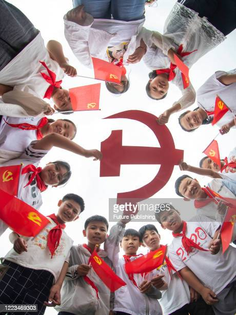 Primary school students hold the party emblem to celebrate the 99th anniversary of the founding of the Communist Party of China. Taizhou City,...