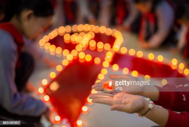 Primary school students light up a red ribbon with candles to raise awareness of the AIDS pandemic on December 1 2017 in Huhhot Inner Mongolia...
