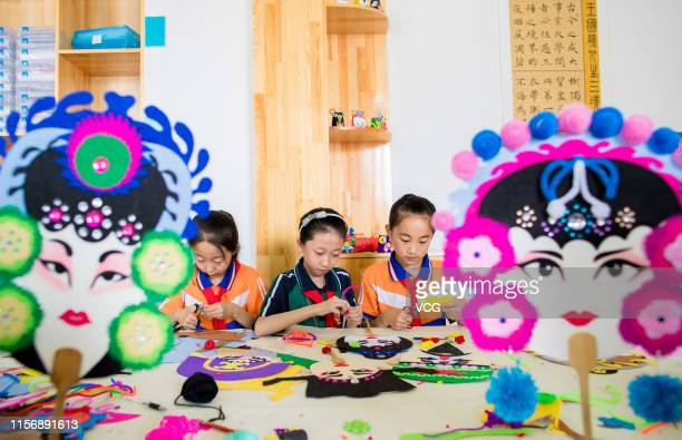 Primary school students make colorful fans featuring opera masks to welcome the summer solstice on June 19 2019 in Hohhot Inner Mongolia Autonomous...