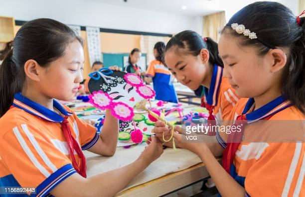 Primary school students make colorful fans featuring opera masks to welcome the summer solstice on June 19, 2019 in Hohhot, Inner Mongolia Autonomous...