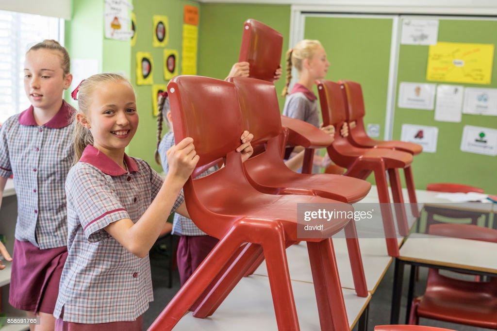 Grundschüler das Aufstellen von Stühlen am Ende der Klasse : Stock-Foto