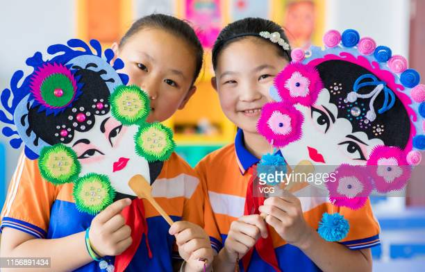 Primary school students show handmade colorful fans featuring opera masks to welcome the summer solstice on June 19 2019 in Hohhot Inner Mongolia...