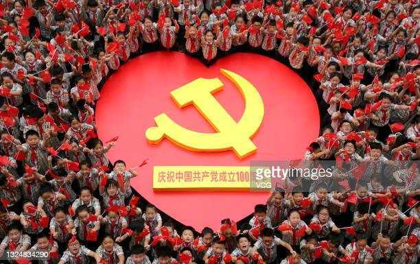 Primary school students sing a song to celebrate the 100th anniversary of the founding of the Communist Party of China on June 22, 2021 in Zaozhuang,...