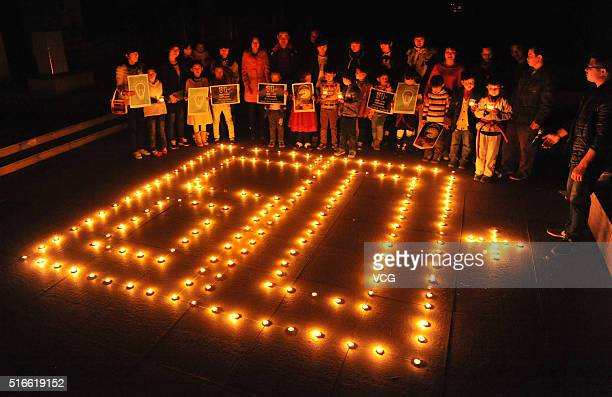 LIN'AN CHINA MARCH 19 Primary school students spell out '60 ' with candles on the 2016 Earth Hour on March 19 2016 in Lin'an Zhejiang Province of...