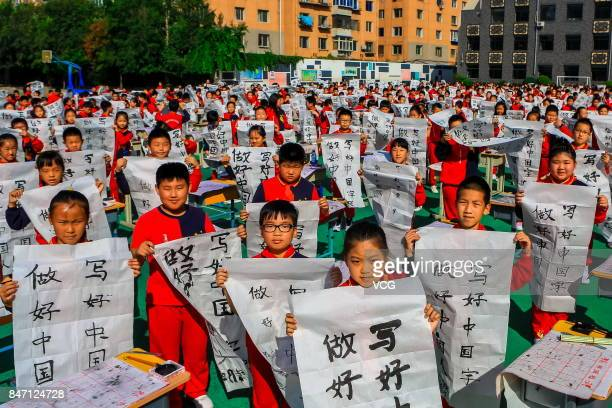 Primary school students write Chinese calligraphy on September 14 2017 in Shenyang Liaoning Province of China About 1000 students attended the grand...