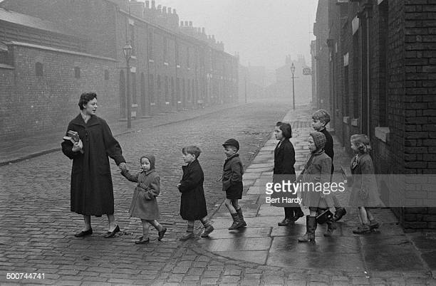A primary school teacher leading a group of children across a road Manchester 16th January 1956 Original publication Picture Post 8223 Teachers In...