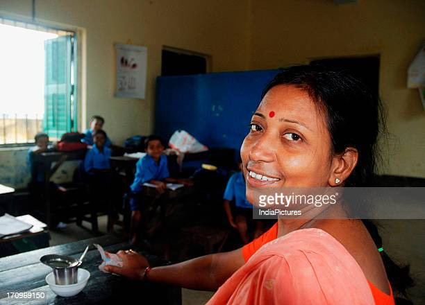 Primary school teacher of slum children from rural areas surrounding Kolkata attending a class, West Bengal, India.