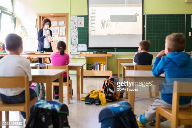 Primary school teacher wearing a face mask as preventive measure teaches a first year class that has been reduced in number of pupils for safety....