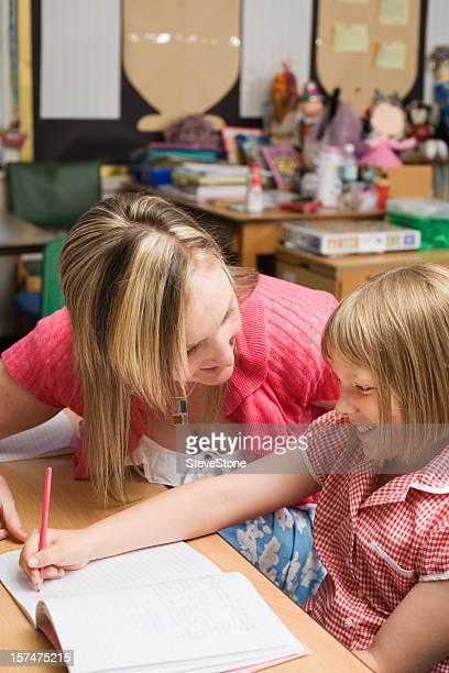 Primary school teacher with girl vertical