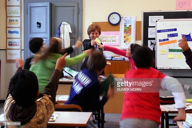 Primary school teatcher Luisa Empilli play with her pupils in her classroom on October 19 2011 in Robecco sul Naviglio western Milan AFP PHOTO /...