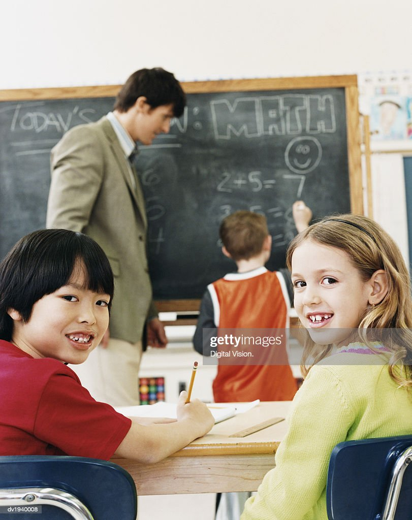 Primary Schoolboy and Schoolgirl Sitting at Desks and a Teacher and Schoolboy in the Background : Stock Photo