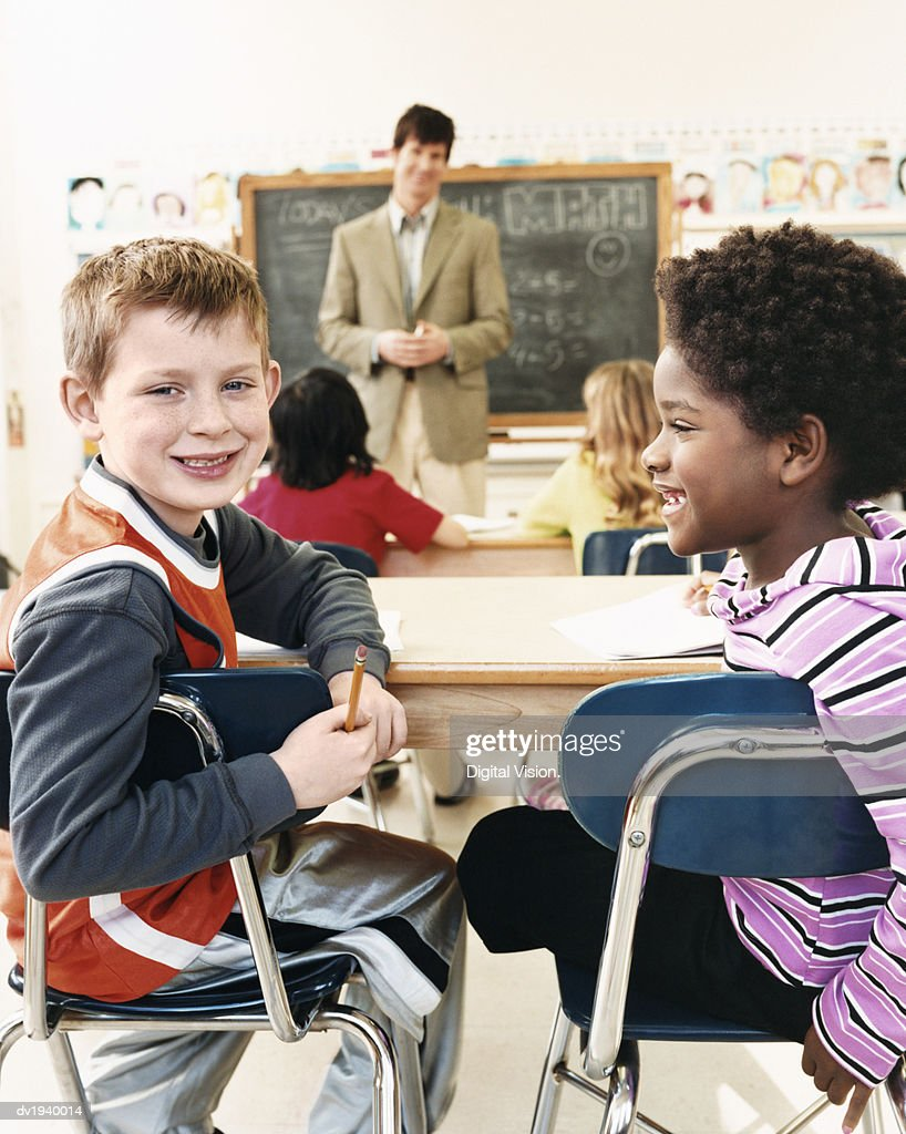 Primary Schoolboy and Schoolgirl Sitting Behind Desks in a Classroom and a Teacher in the Background : Stock Photo