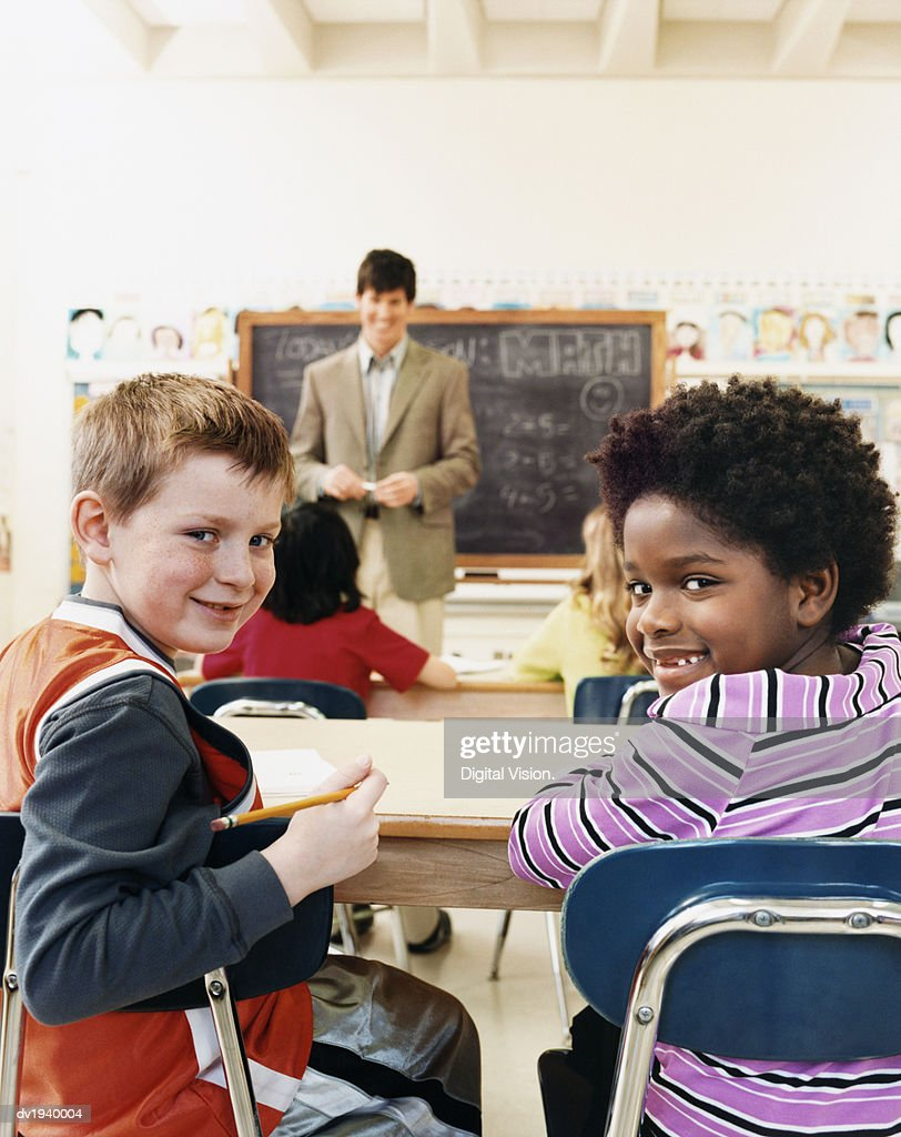 Primary Schoolboy and Schoolgirl Sitting in a Classroom With a Teacher in the Background : Stock Photo