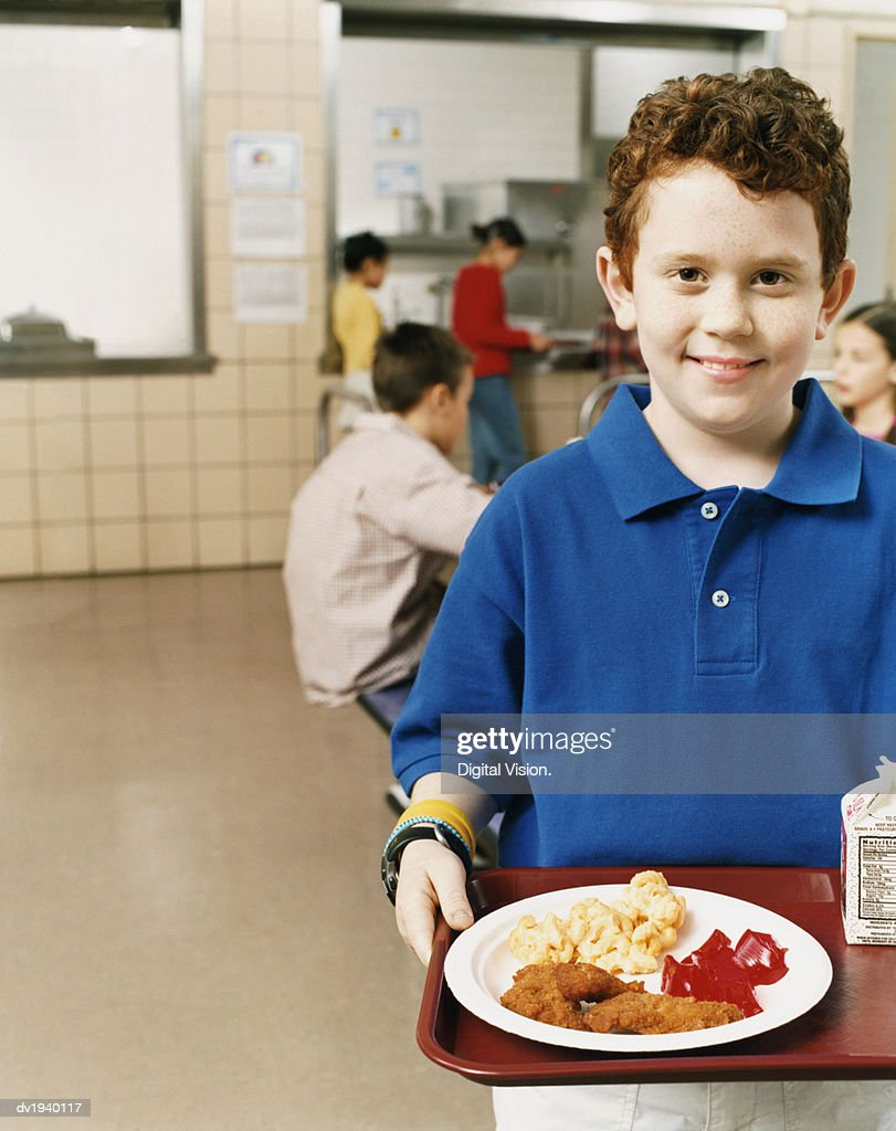 Primary Schoolboy in a Canteen Holding a Tray With a Plate of Unhealthy Food : Stock Photo