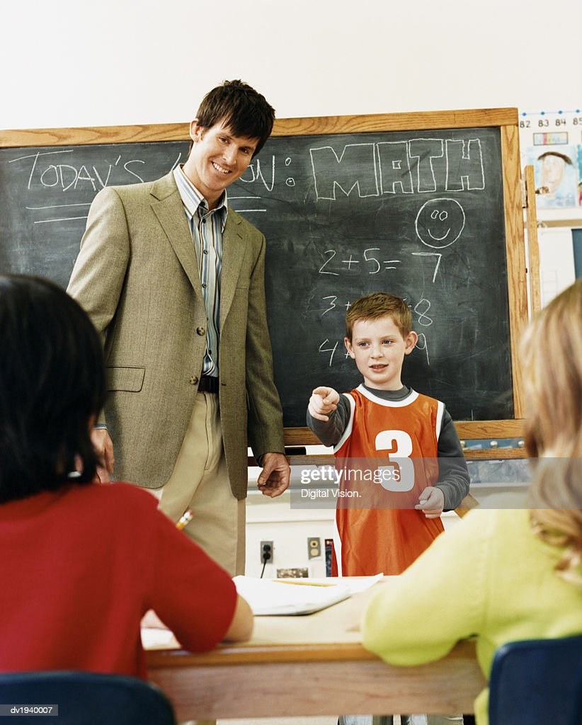 Primary Schoolboy in a Classroom Standing Next to a Teacher Pointing to Another Pupil : Stock Photo