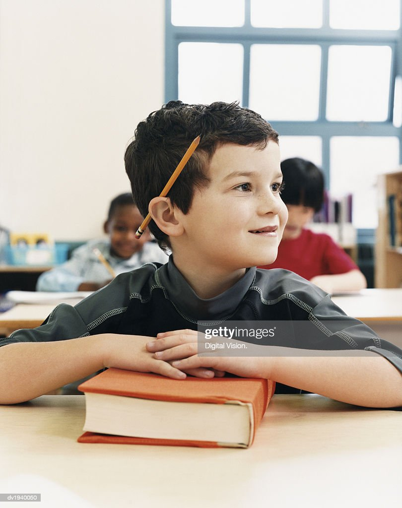 Primary Schoolboy Sitting at His Desk and Looking Sideways : Stock Photo