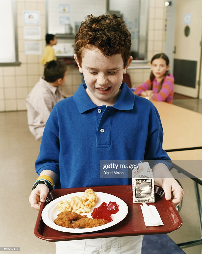 Primary Schoolboy Standing in a School Canteen Holding an Unhealthy School Meal : Stock Photo