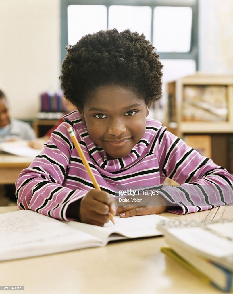 Primary Schoolboy Writing in His Exercise Book in a Classroom : Stock Photo