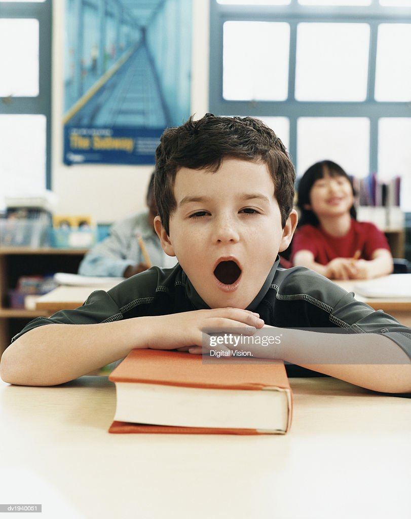 Primary Schoolboy Yawning at His Desk in a Classroom : Stock Photo