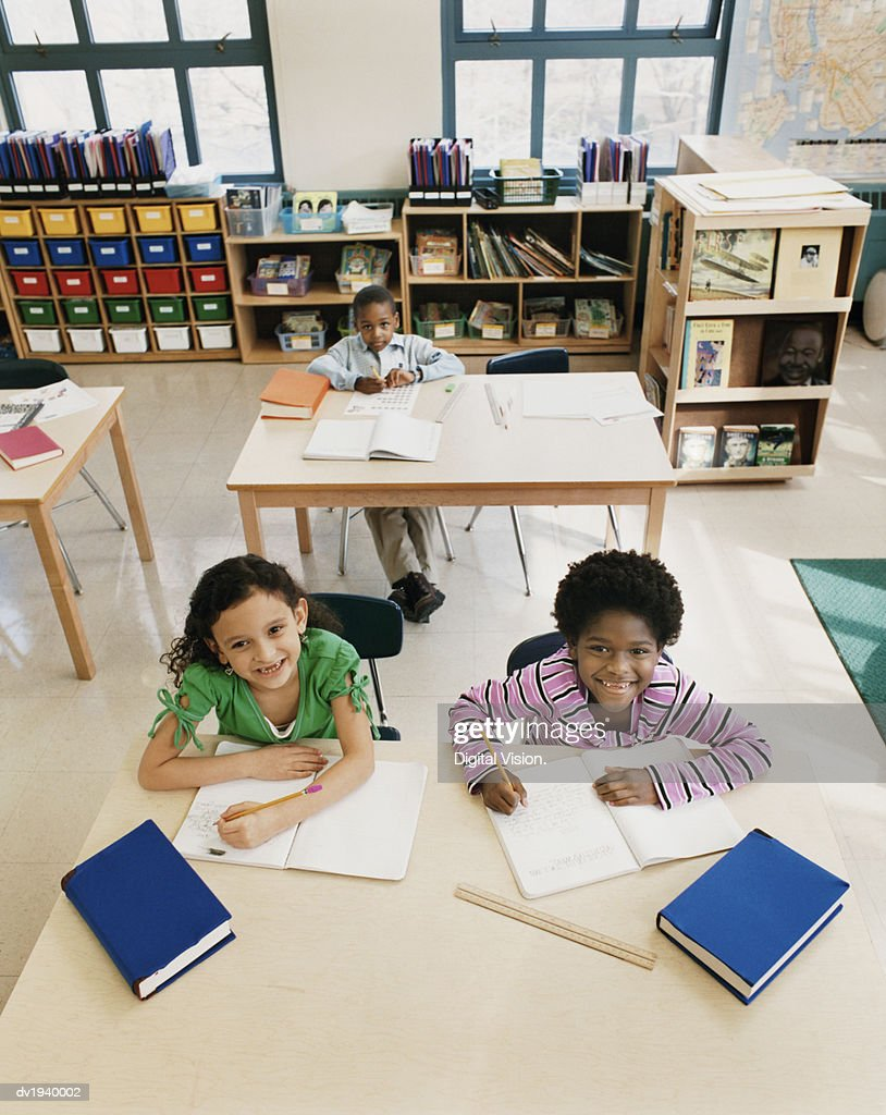 Primary Schoolboys and Schoolgirls Sitting Behind Tables in a Classroom Studying and Writing in Exercise Books : Stock Photo