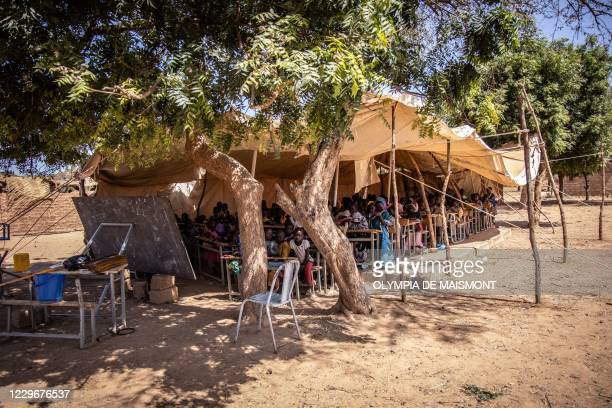 Primary schoolchildren sit in a classroom under a tent put in place to face the rising arrival of children, at Koum-Lakre school, located in Kaya's...