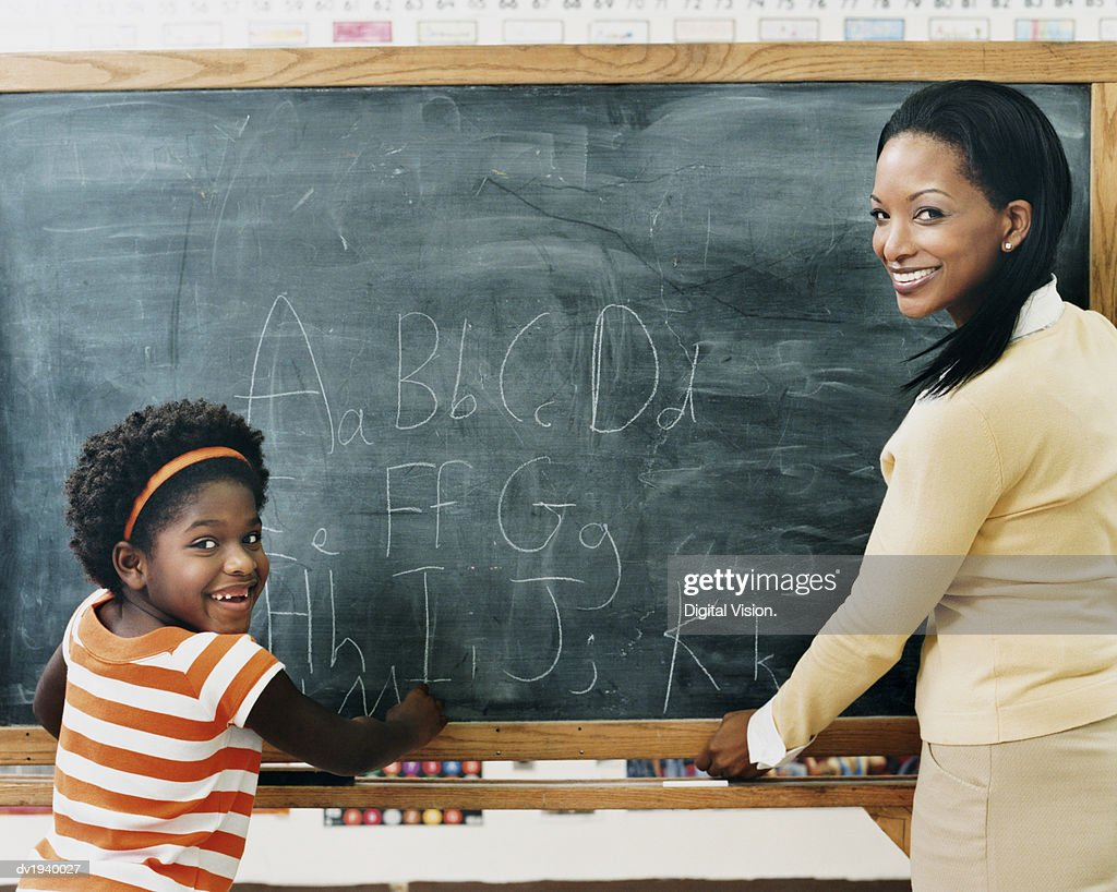 Primary Schoolgirl and Her Teacher Standing in Front of a Blackboard in a Classroom : Stock Photo
