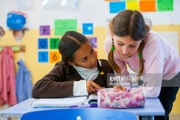 Primary schoolgirl helping friend with workbook in classroom