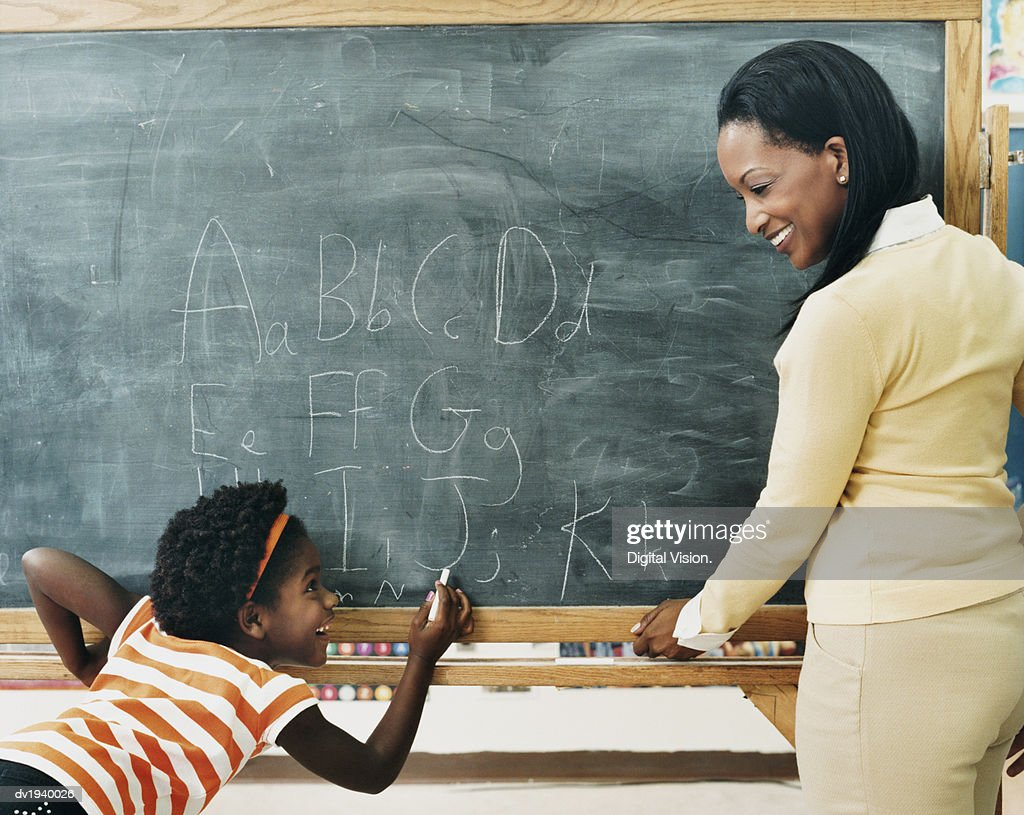 Primary Schoolgirl in a Classroom Writing on a Blackboard and a Teacher Watching : Stock Photo
