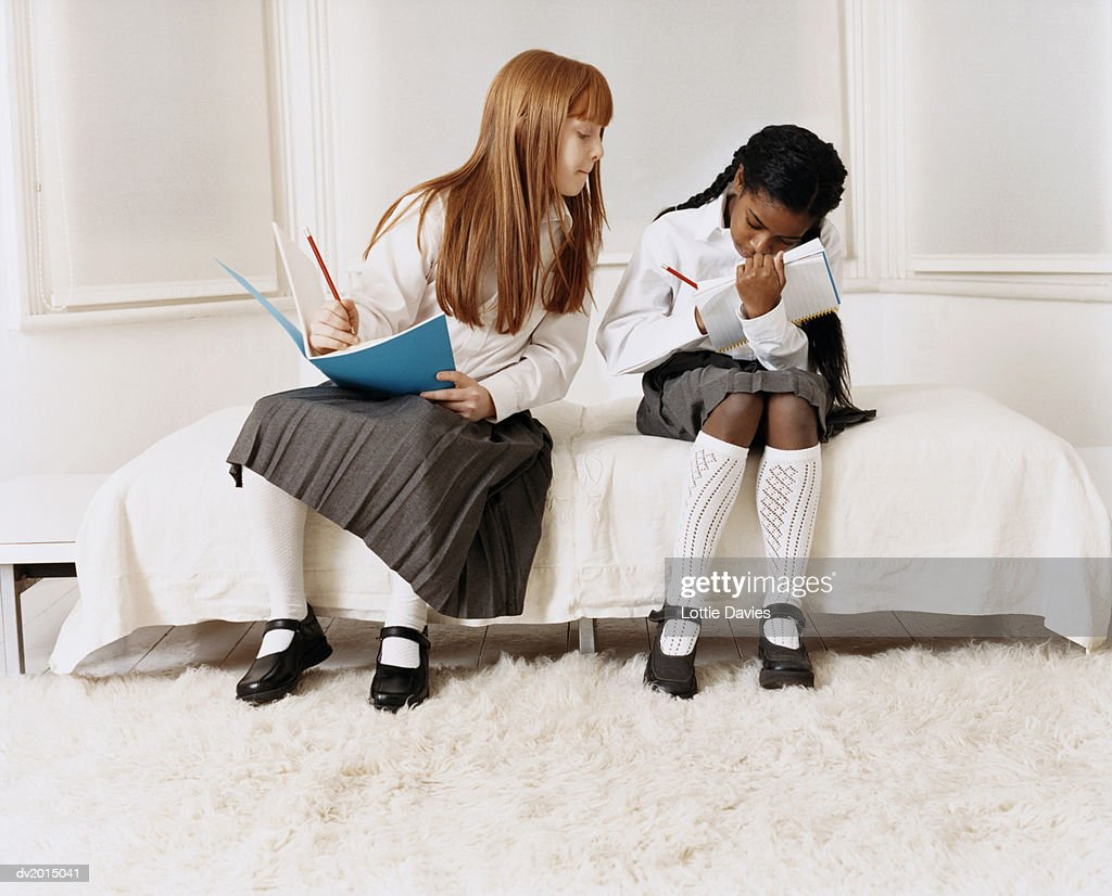 Primary Schoolgirl Sitting Next to a Schoolgirl in a Bedroom Watching Her Writing in an Exercise Book : Stock Photo