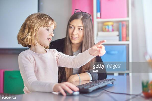 primary schoolgirl using a  computer with her teacher