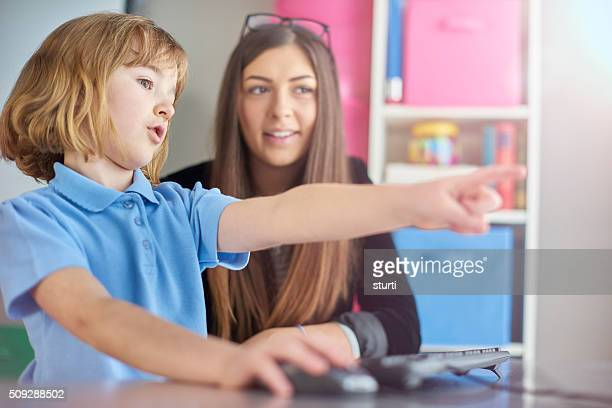 primary schoolgirl using a  computer with her teacher