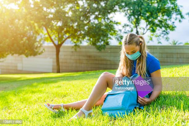primary student girl sitting on grass wearing protective face mask - reopening stock pictures, royalty-free photos & images