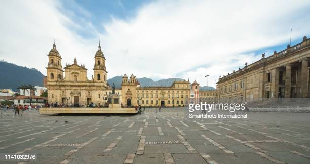 primatial cathedral of bogotá on bolivar square of bogota with capitolio nacional on the right hand side in bogota, colombia - bogota stock pictures, royalty-free photos & images