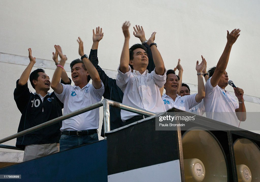 Prime Minister Abhisit Vejjajiva cheers with party members on top of a truck at his last political event before the vote in the country's 4th election in 7 years, on July 2, 2011 in Bangkok, Thailand. The vote pits Prime Minister Abhisit Vejjajiva's Democrats against Thaksin's younger sister, Yingluck Shinawatra, who has the full support of the red shirt followers of fugitive former premier Thaksin Shinawatra, who was ousted in a 2006 coup.
