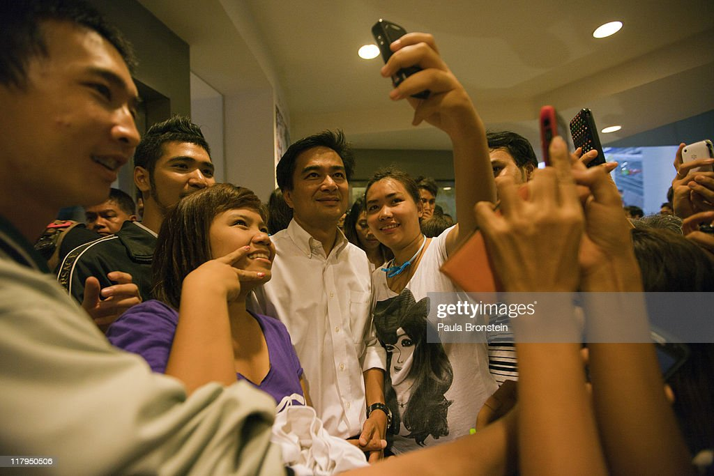 Prime Minister Abhisit Vejjajiva poses with young Thai supporters after arriving at his last political event before the vote in the country's 4th election in 7 years, on July 2, 2011 in Bangkok, Thailand. The vote pits Prime Minister Abhisit Vejjajiva's Democrats against Thaksin's younger sister, Yingluck Shinawatra, who has the full support of the red shirt followers of fugitive former premier Thaksin Shinawatra, who was ousted in a 2006 coup.