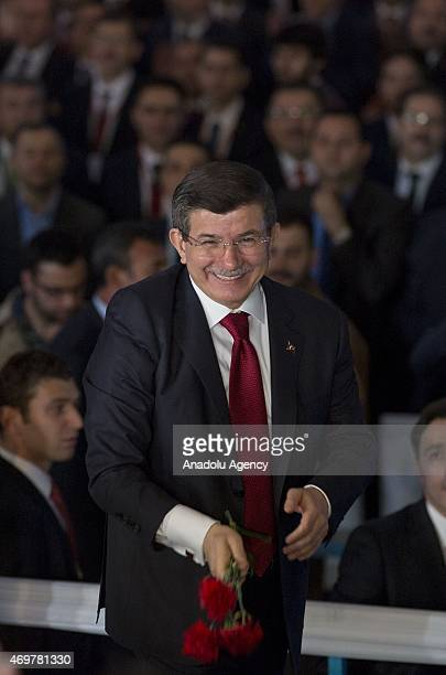 Prime Minister and AK Party Chairman Ahmet Davutoglu throws red carnations to the AK Party supporters as he arrives for the event of the Justice and...