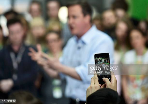 Prime Minister and leader of the Conservative Party David Cameron is seen on the screen of a smartphone as he addresses workers at the head office of...