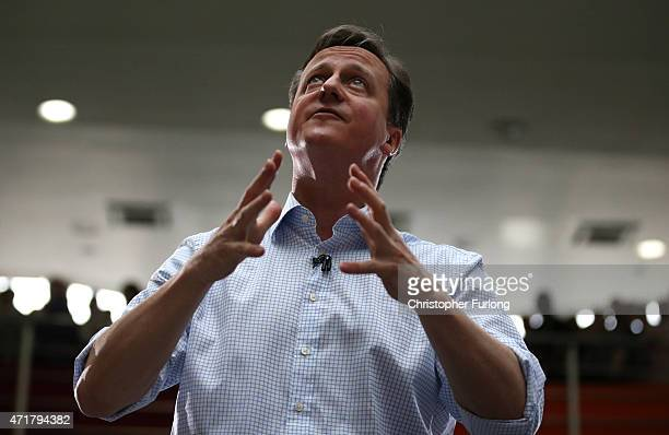 Prime Minister and leader of the conservatives David Cameron looks up to an audience in the balcony as he addresses workers at the head office of...