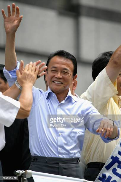 Prime Minister and President of the Liberal Democratic Party Taro Aso waves to the audience upon his arrival for a stump speech during an election...