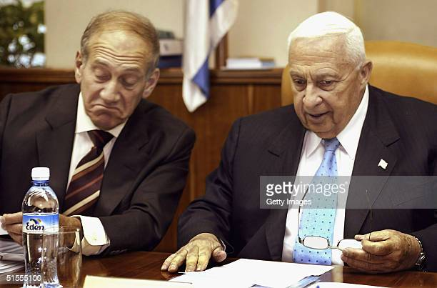 Prime Minister Ariel Sharon listens to his Deputy Prime Minister Ehud Olmert who frowns as the weekly cabinet meeting comes to order in Sharon's...