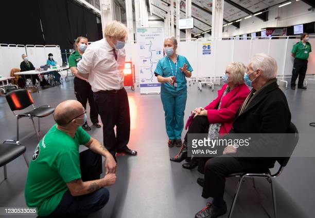 Prime Minister Boris Johnson accompanied by Head Nurse Anne Morris speaks to Hazel and John Watson as he visits a vaccination centre at Ashton...