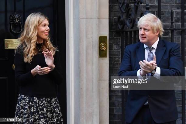 Prime Minister Boris Johnson and his fiancée Carrie Symonds applaud for key workers outside 10 Downing Street on May 14 2020 in London England...