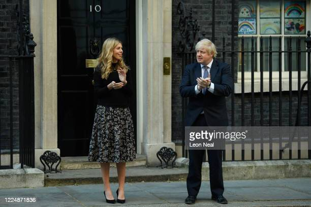 Prime Minister Boris Johnson and his fiancée Carrie Symonds applaud for key workers outside 10 Downing Street on May 14, 2020 in London, England....