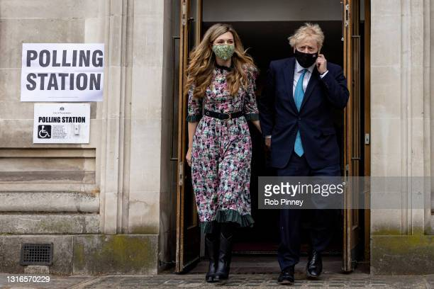 Prime Minister Boris Johnson and his fiancée Carrie Symonds leave Methodist Central Hall in Westminster after voting on May 06, 2021 in London,...