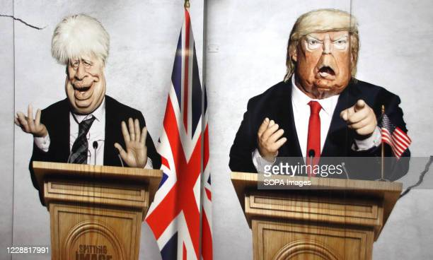 Prime Minister Boris Johnson and US President Donald Trump are pictured in this panel. Caricatures of politicians on large advertisement board for...