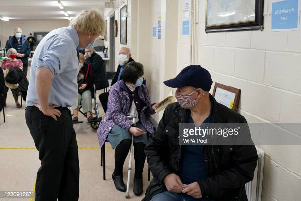 Prime Minister Boris Johnson attempts to engage with a waiting patient as he visits a COVID-19 vaccination centre in Batley, on February 1, 2021 in...