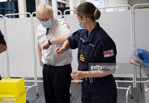 Prime Minister Boris Johnson bumps elbows with a member of the Navy team training to vaccinate as he visits a vaccination centre at Ashton Stadium on...